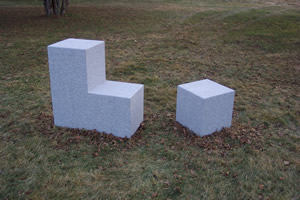 Granite Chair / Stool Cutout - With one intervention, a simple cube becomes a chair and the cut-out remainder becomes a stool: an evocation in granite of the living room easy chair. I envision a grouping of these functional sculptures scattered around a courtyard or building lobby.Material: GraniteApproximate dimensions 3' Ht.x 6'x 2' ( 2 pieces)