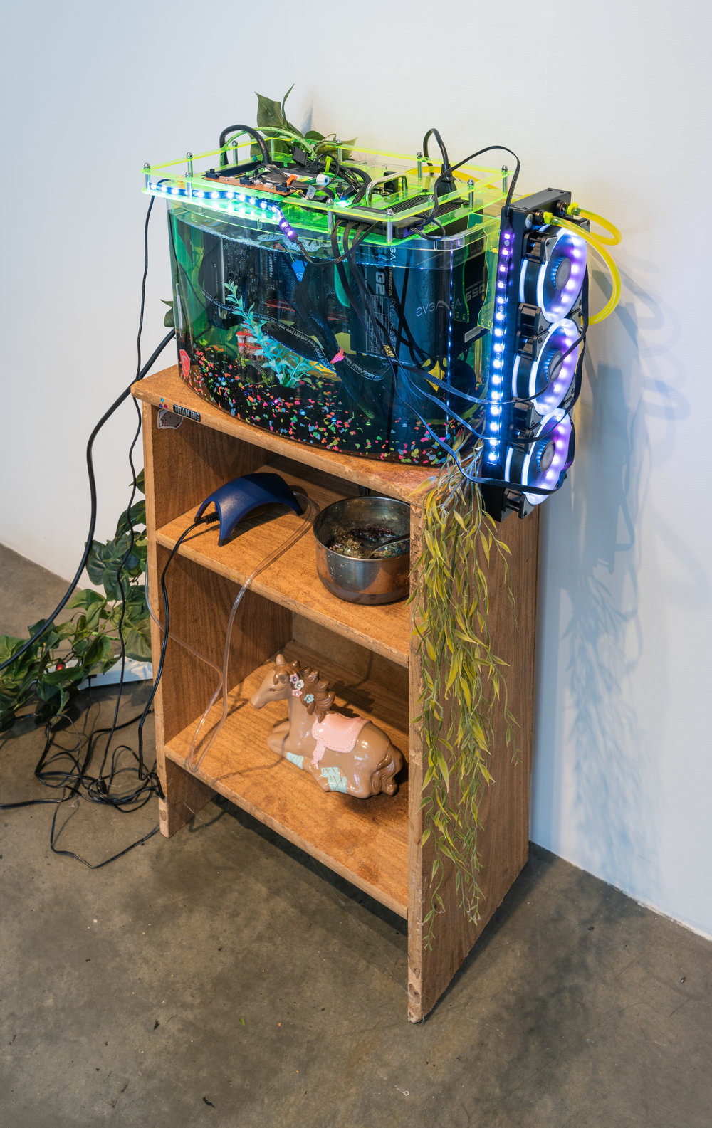 A Rich Inner Life , 2018  Custom gaming computer in aquarium with mineral oil set on found shelf with various found objects  Dimensions variable