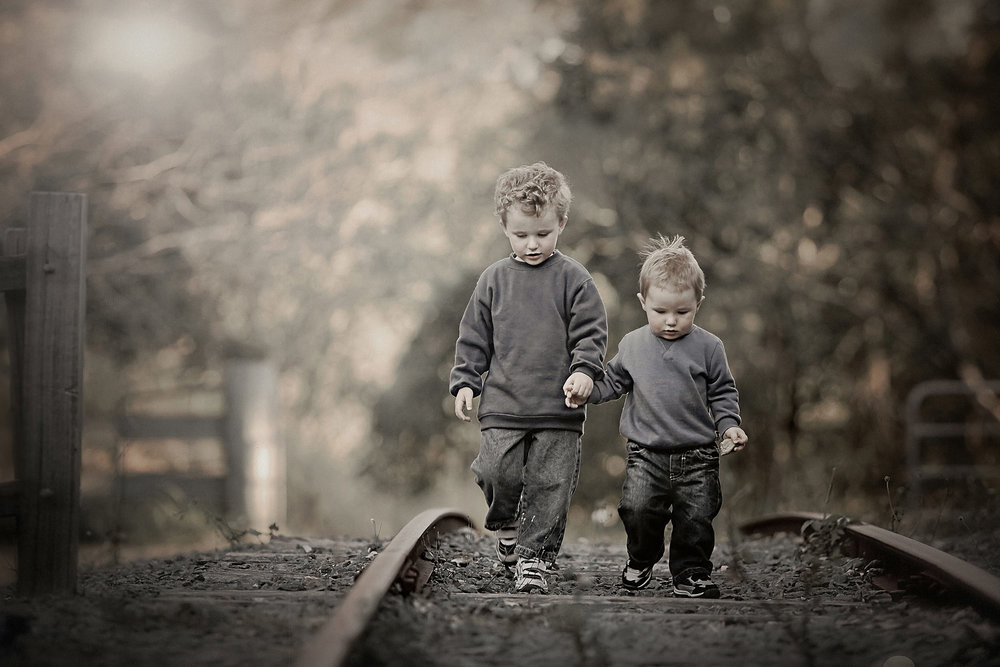 desaturated colour portrait of brothers on railway track-learn natural light portraits.jpg