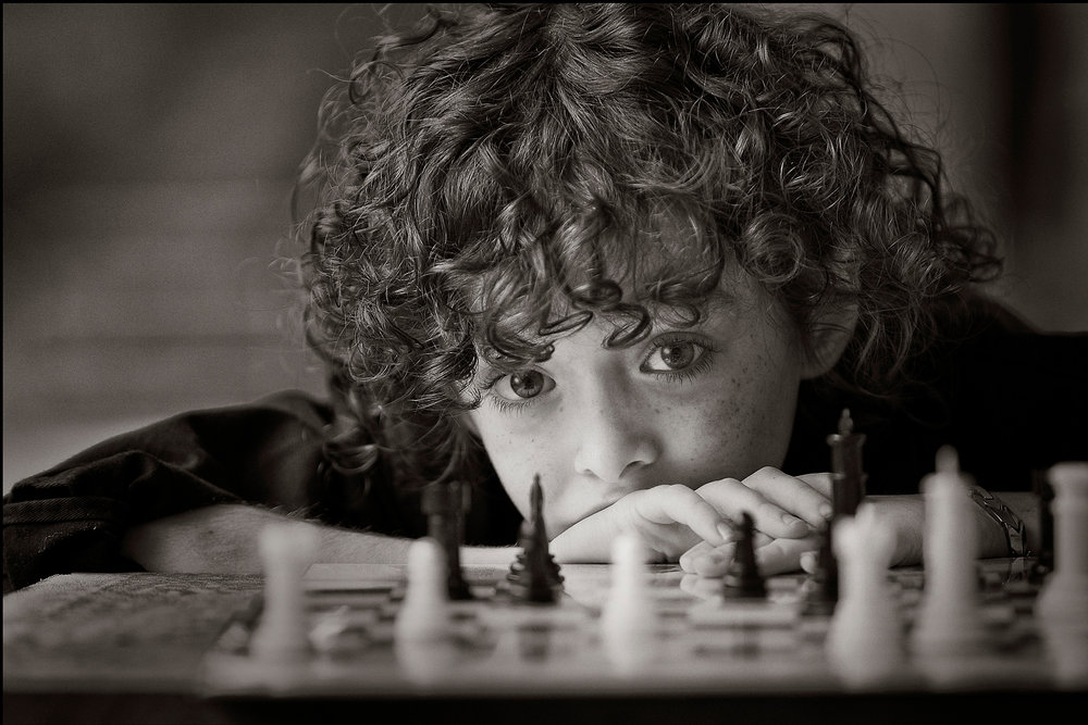 free natural light portrait tutorials-black and white portrait of boy playing chess -soulful portrait.jpg