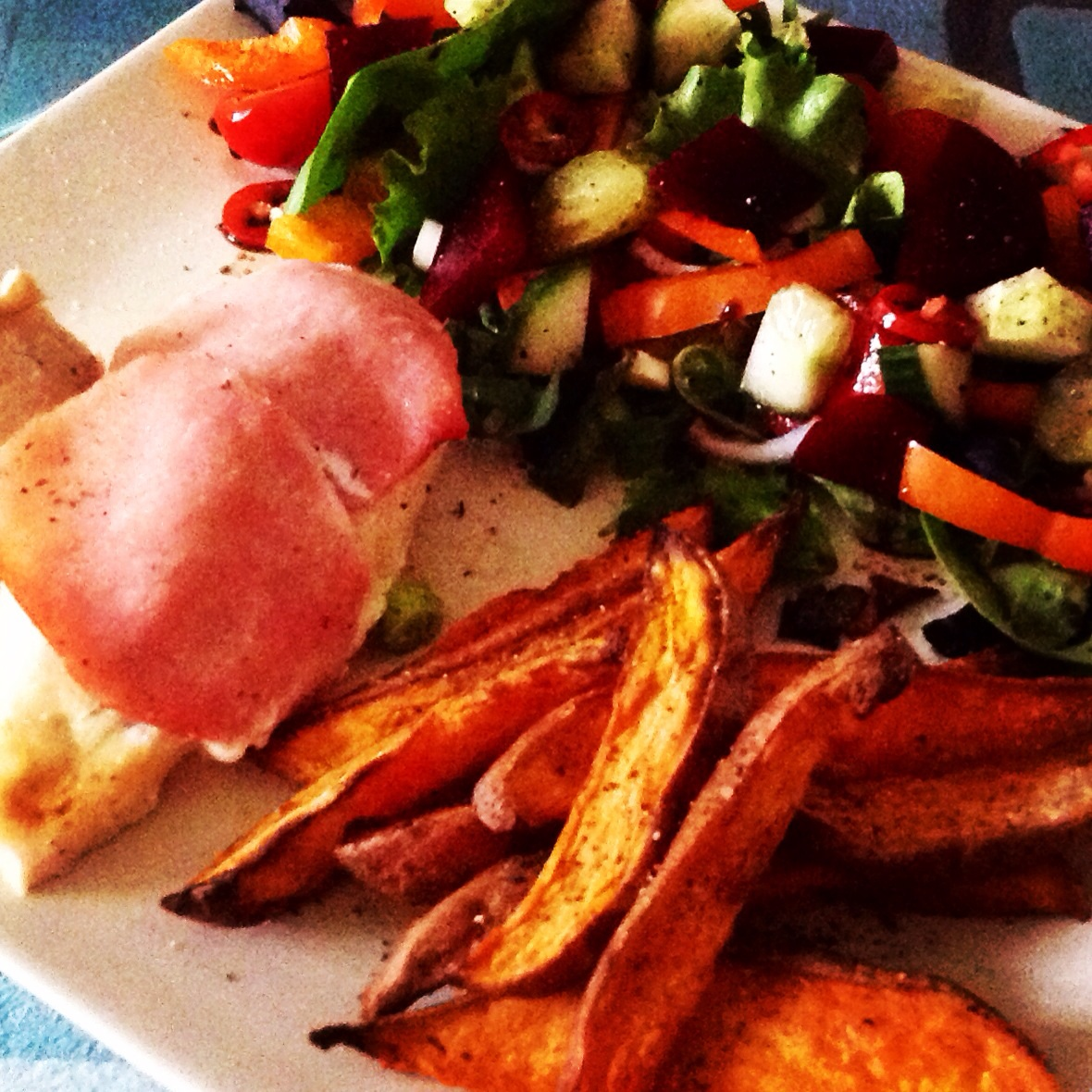Chicken stuffed with quark and garlic wrapped in bacon, sweet potato chips and salad