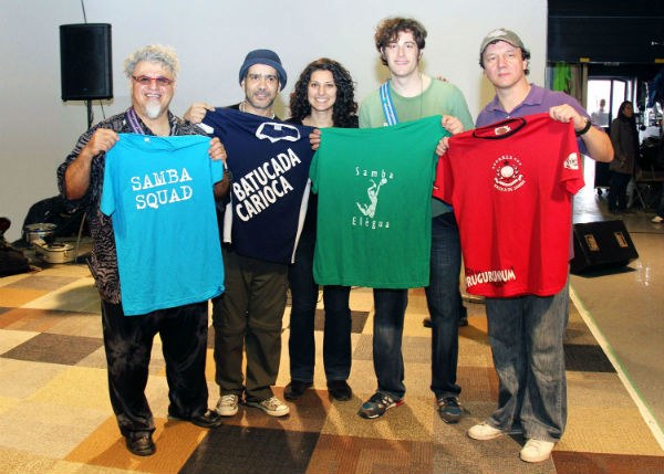 The group leaders show off the four t-shirts of the four Toronto samba bateria groups