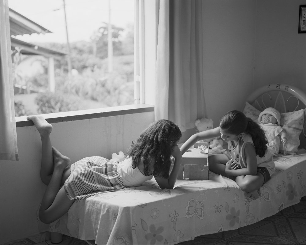 Ivna and Lara playing house inside the Farias family home at company housing complex Vila 4, April, 2014, Michelin Rubber Plantation, Bahia, Brazil. 2014/2018