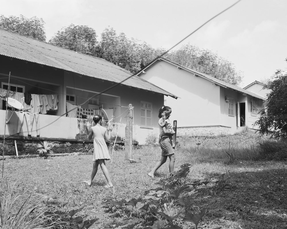 Sisters Ivna and Ingrid Souza playing with cousin Monick Farias in the family backyard with squash plants in the foreground at company housing complex Vila 4, April, 2014, Michelin Rubber Plantation, Bahia, Brazil. 2014/2018