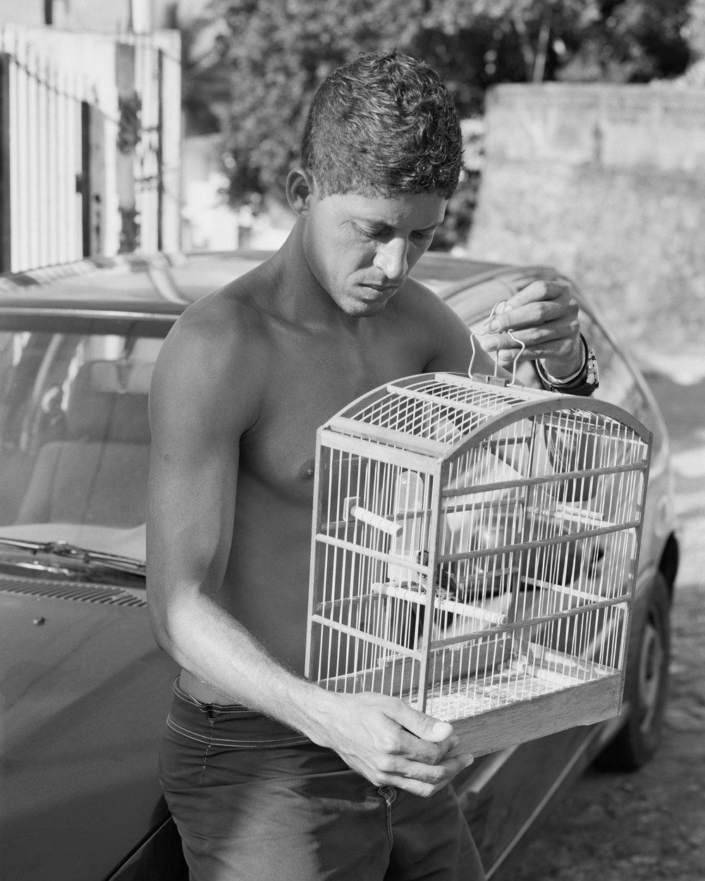 Fábio Santos resting on car with birdcage, March, 2014, Itaparica, Brazil. 2014/2018