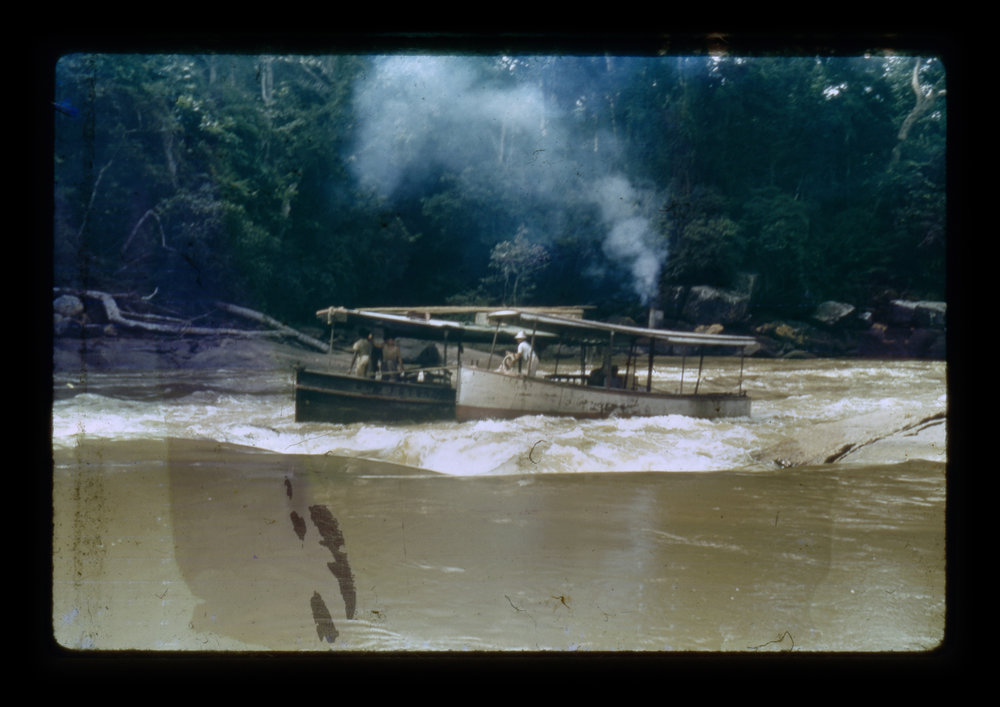 """(research image) Untitled, Porto Velho, Brazil (1921-1952). Typed on verso: """"R 8-10 Our launch & batalau coming into swift set of rapids."""" 35mm Kodachrome Slide. Creator: Cortland B. Manifold. Courtland Manifold Papers, Archival Services, University Libraries, The University of Akron, Akron, Ohio"""