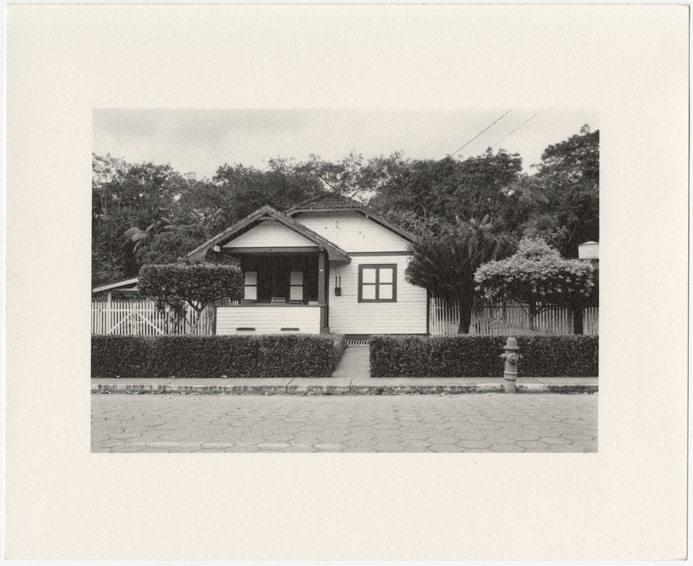 """Belterra employee house with trimmed hedges and fire hydrant, built in 1934 by the Companhia Ford Industrial Do Brasil Ford Motor Company. 2014 Belterra, Pará, Brazil. Gelatin silver fiber print,  8"""" x 10"""", 2014/2018"""