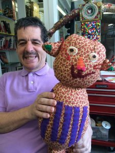 Artist Charles holding soft sculpture 'Butters the Cat'.