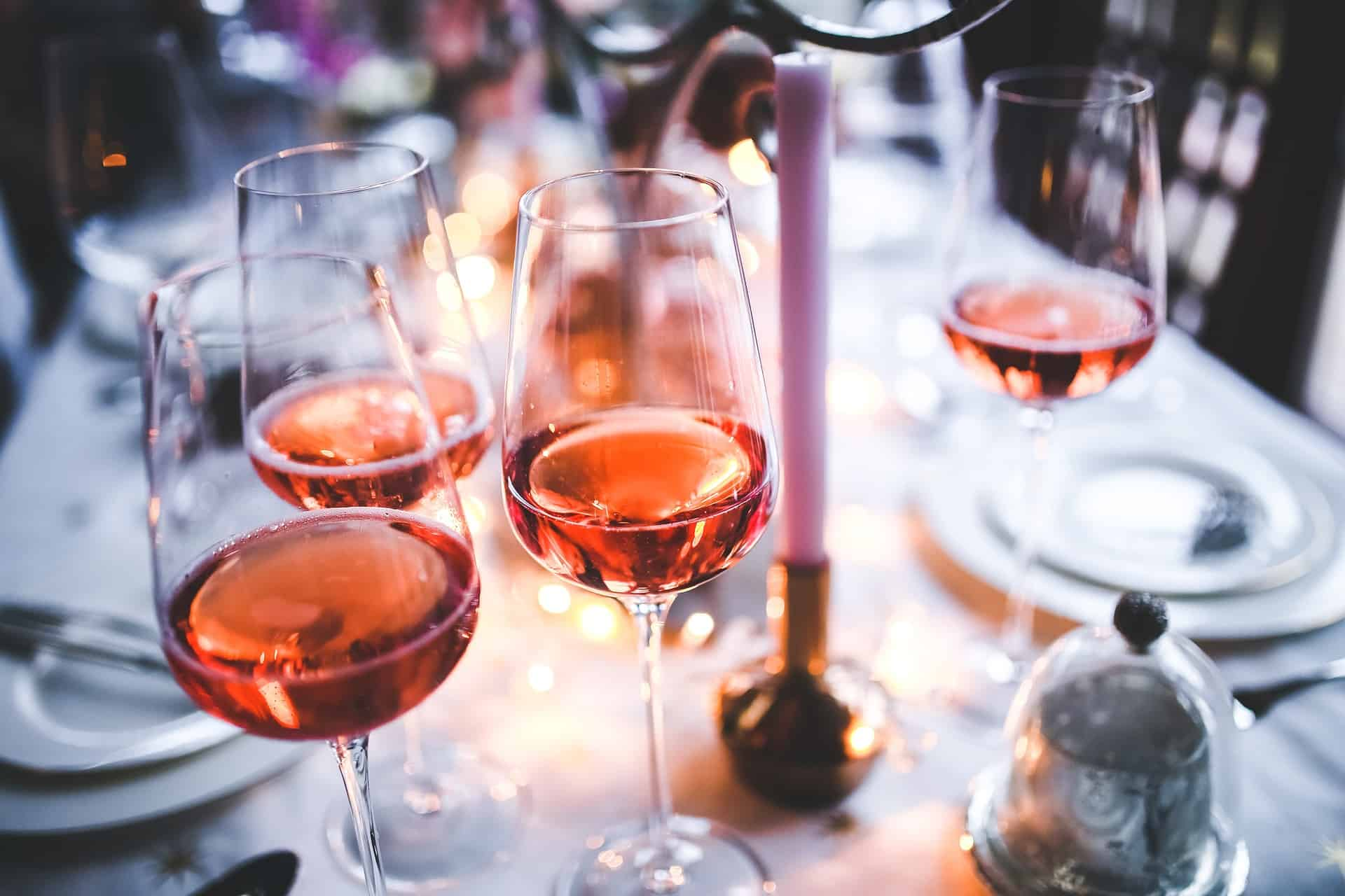 A white tablescape with 4 glasses of rose wine