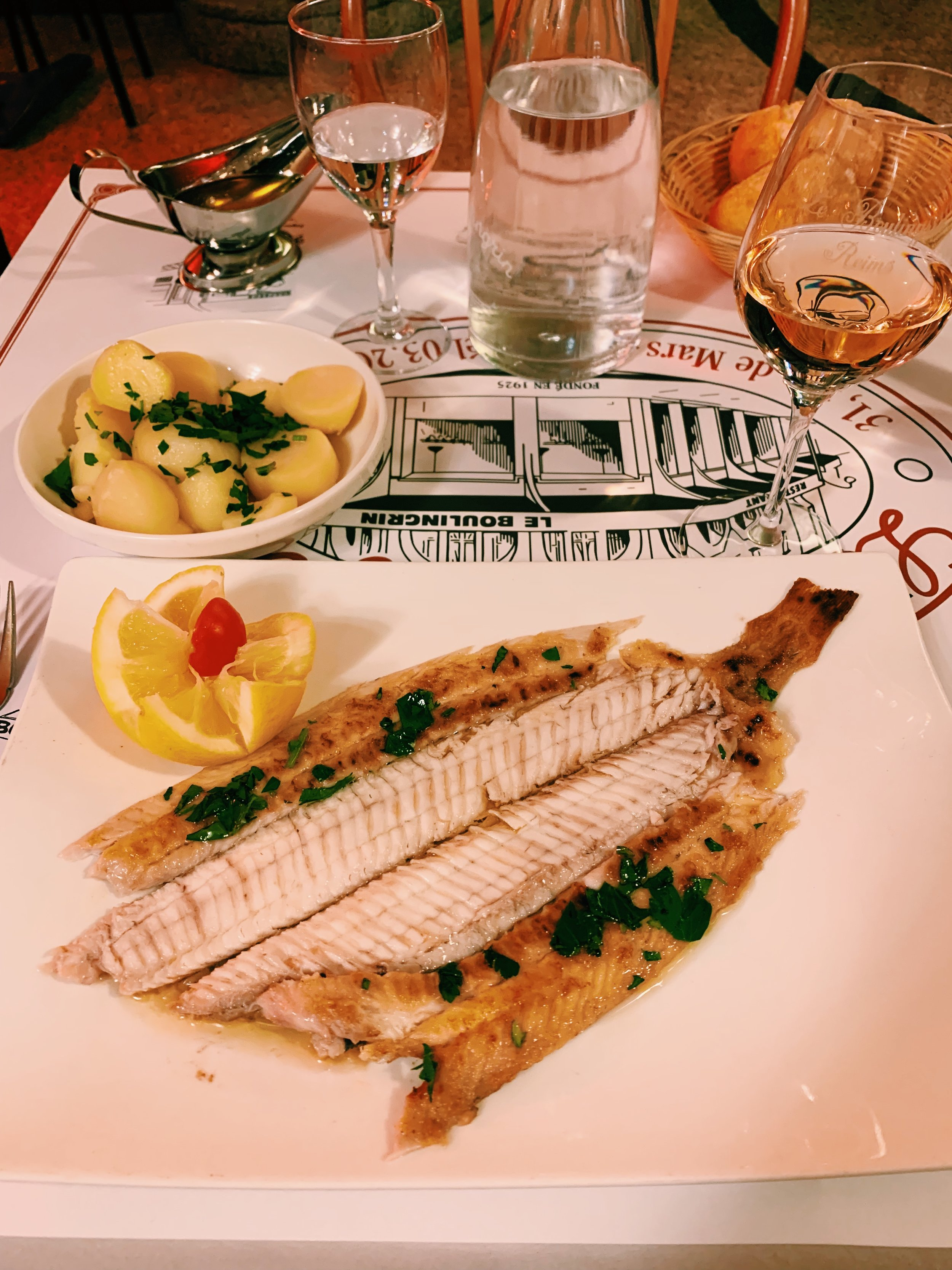 sole meunier at a brasserie with potatoes and a glass of rose champagne