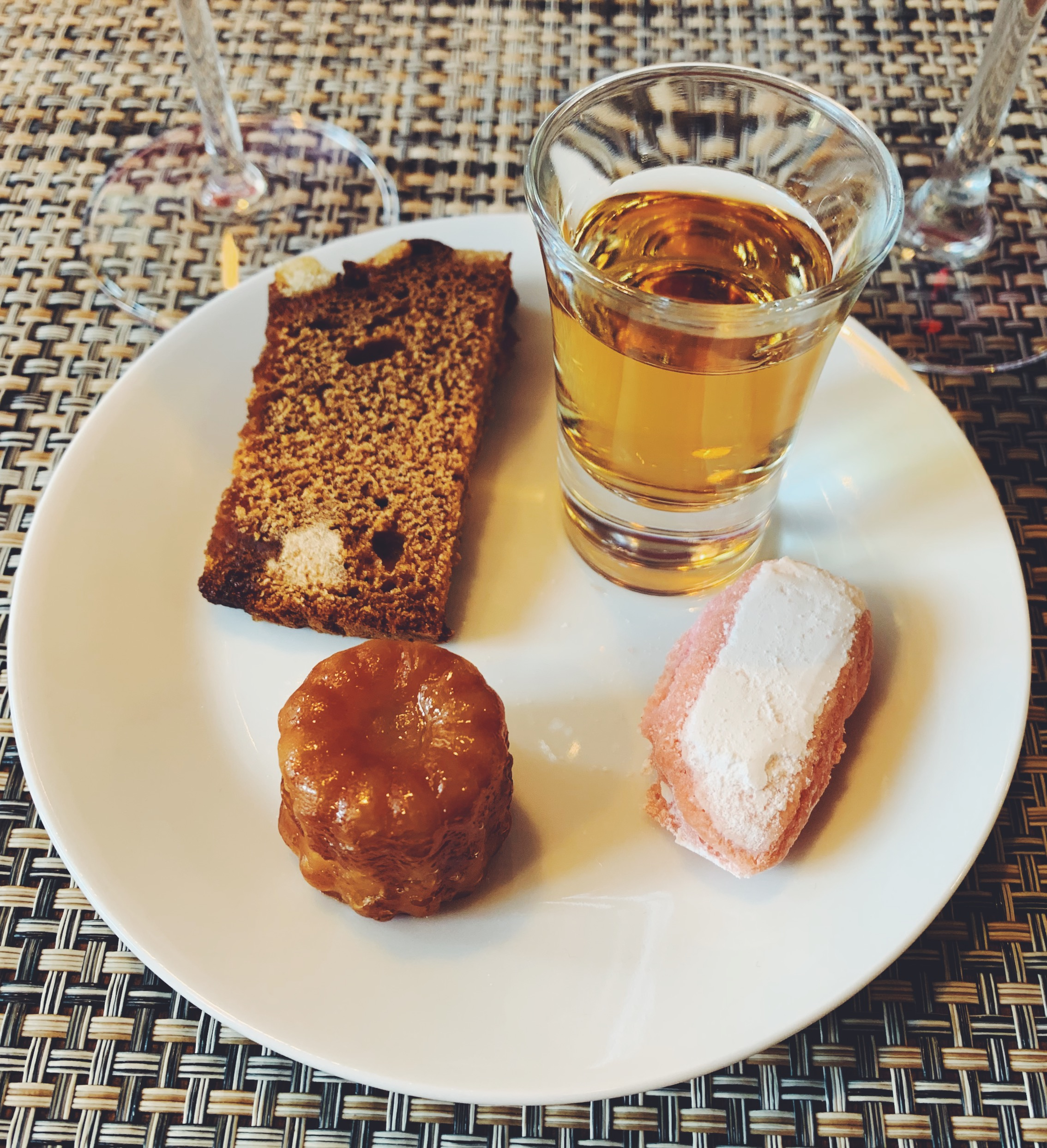 a setting of ratafia in a shot glass, a rose biscuit from reims, a canele, and a small slice of ginger bread
