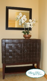 a mirror hanging above a credenza with a potted orchid