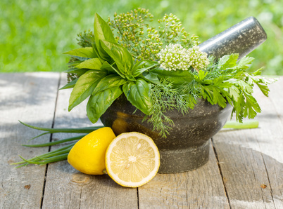 sliced lemon next to a mortar and pestle with herbs