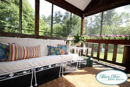outdoor sofa with throw pillows on ascreened porch