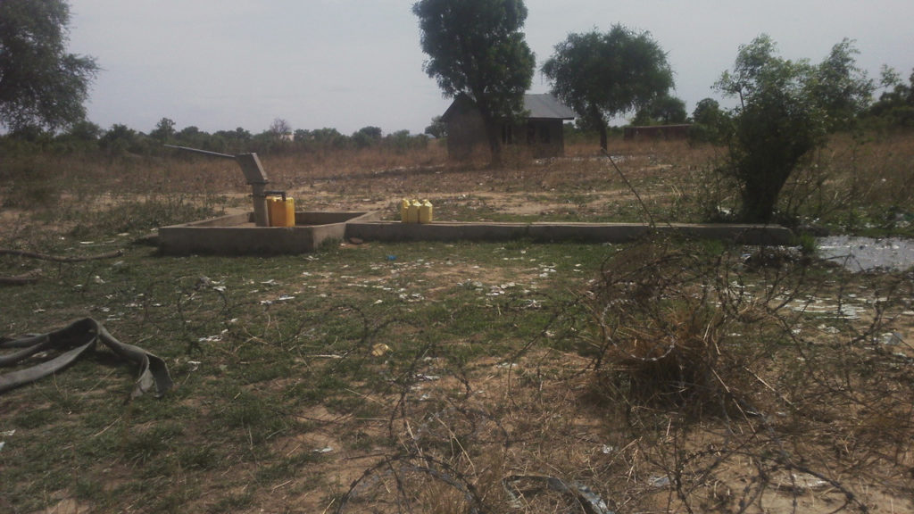 The water well on ASC land in Bor, Jonglei State, South Sudan. Abandoned building in background.
