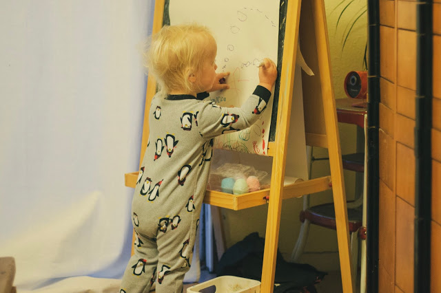 A toddler-age artist carefully draws a rendition of Cookie Monster on an IKEA easel.