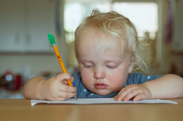 Toddler-age boy drawing with a pencil at the table