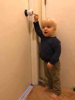 Toddler-age blond boy trying to pick lock to his older brother's room.