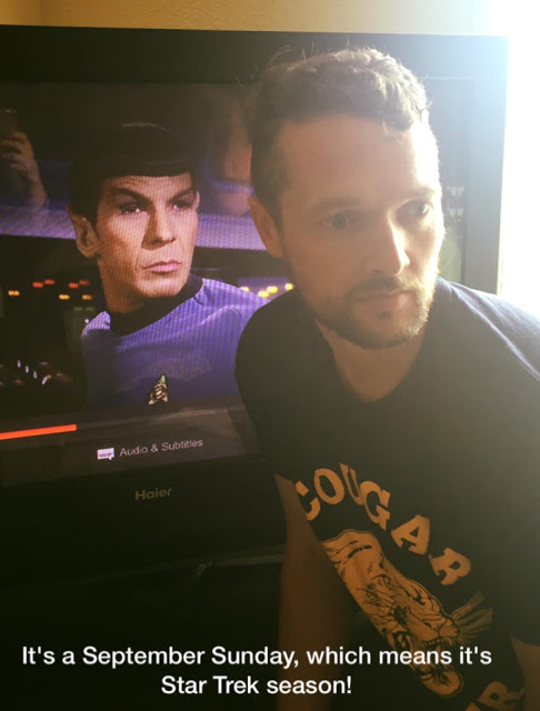 Male who looks nothing like Spock standing in front of television screen with Spock staring at him