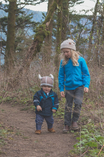 Older brother hiking with toddler-age brother wearing Viking hat in the Columbia Gorge forest.
