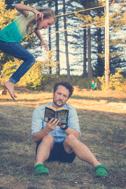 Daughter leaping over her father while he reads in the grass