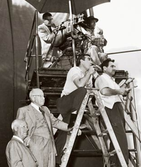 Anthony directing  The Buccaneer  from atop ladder, with Cecil B. DeMille watching from directly below, left, 1958