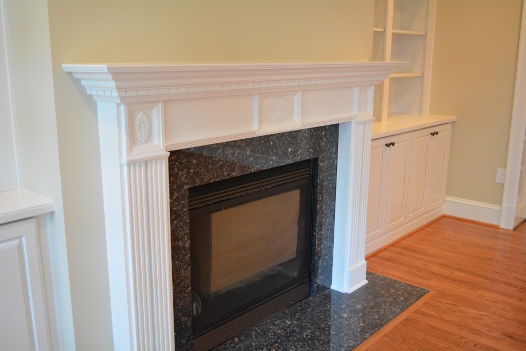 The gas fireplace with granite surround and custom mantle is the focal point of the room. The semi custom bookcases on either side give the space the character the homeowners wanted.