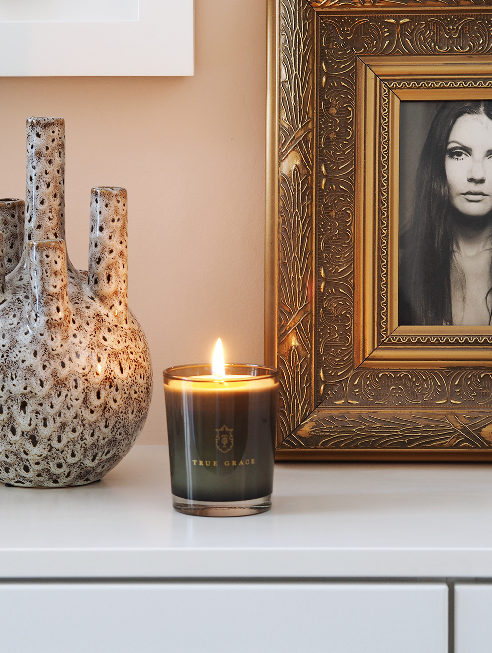 My Summer Dining Room - French For Pineapple Blog - close up of lit scented candle on sidebaord with lung like vase object and ornate framed photograph