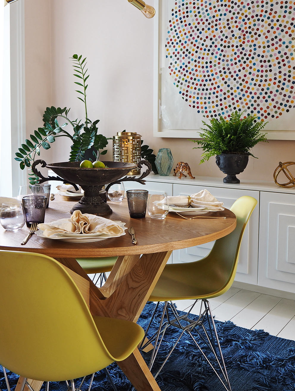 My Summer Dining Room - French For Pineapple Blog - Medium wide shot of dining room with round wooden mid century style table, eames chairs, blue shaggy rug and smart casual table setting and side board with stepped panelled doors