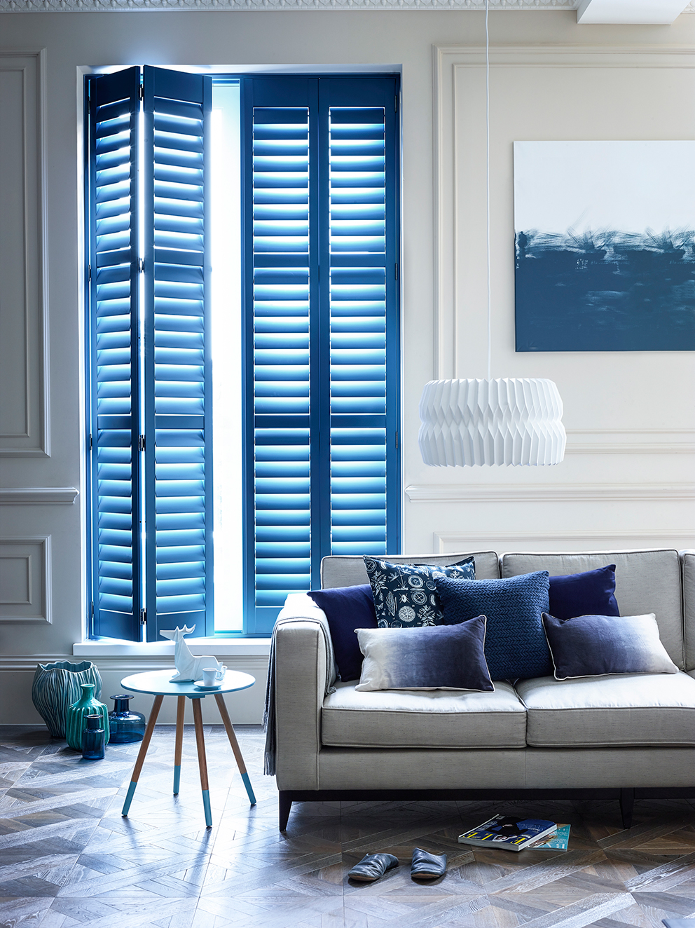 Shutterly Fabulous - French For Pineapple Blog - full lenght blue shutters in traditional room with wall moulidng and parquet floor with modern sofa