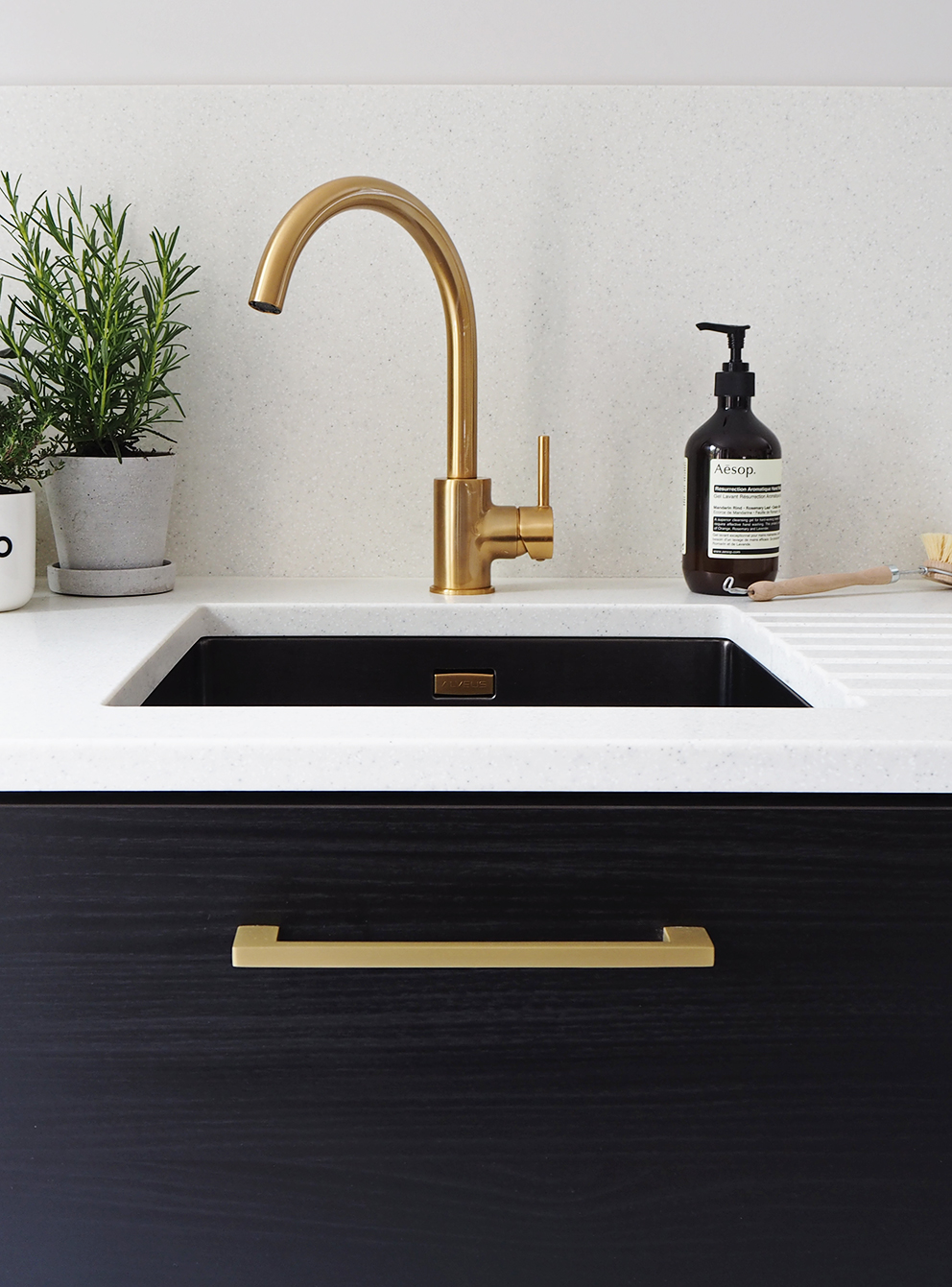 French For Pineapple Blog - brass gold contemporary tap and undermounted sink, black wood grain units and satin brass handle with herbs on the pale flecked mistral mist worktop and splashback