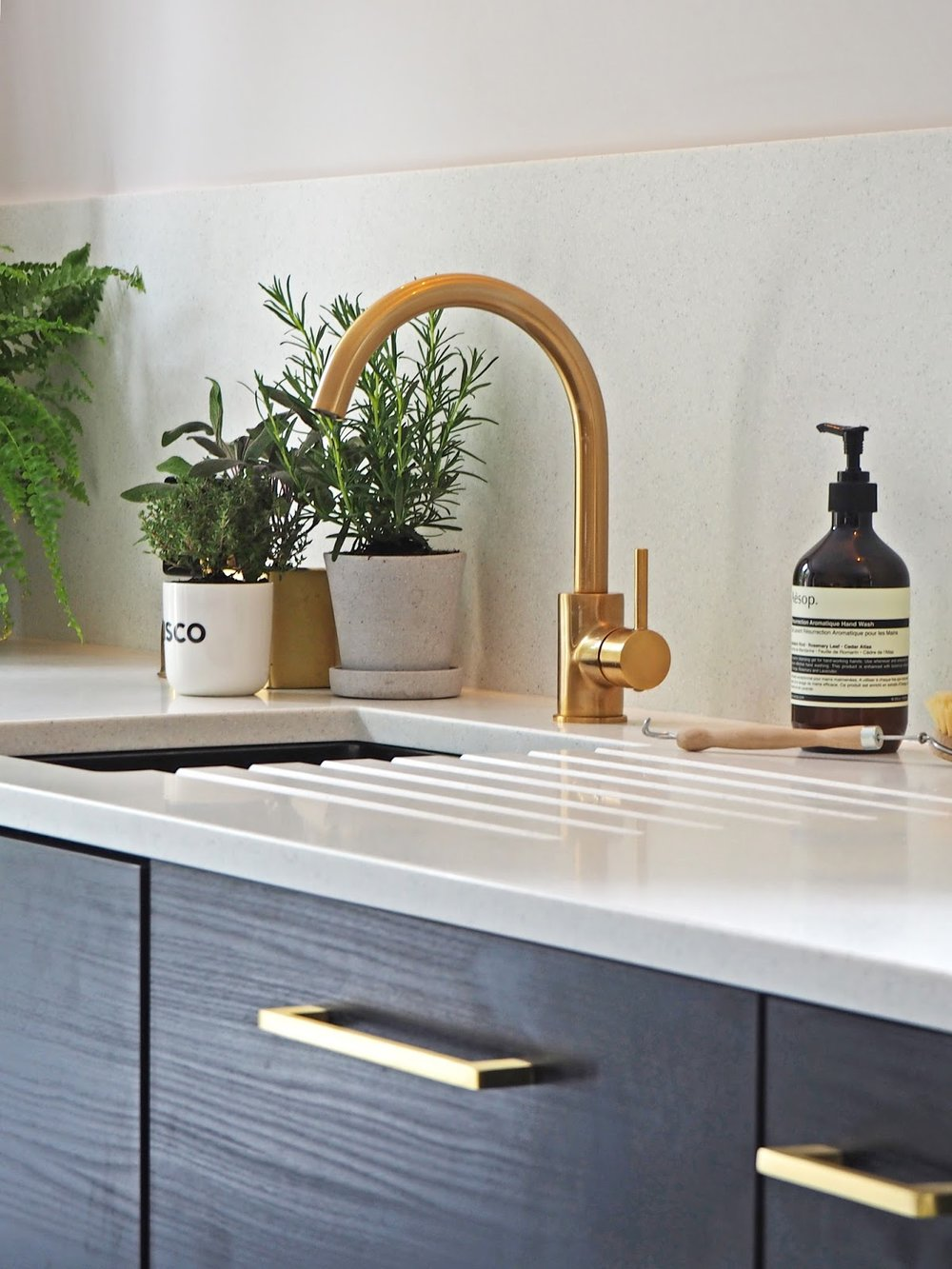 French For Pineapple Blog - contemporary gold tap and undermounted sink with pale flecked mistral mist worktops, black wood grain cupboards and satin brass handles. Herbs and aesop soap on worktop.