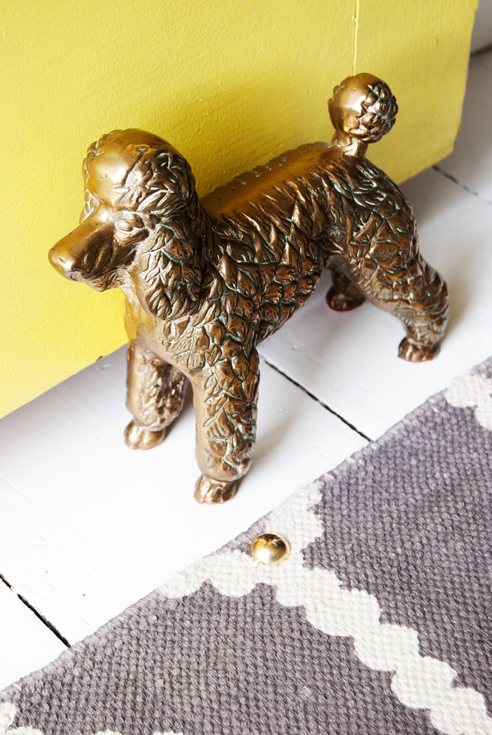 Brass poodle doorstop and yellow door