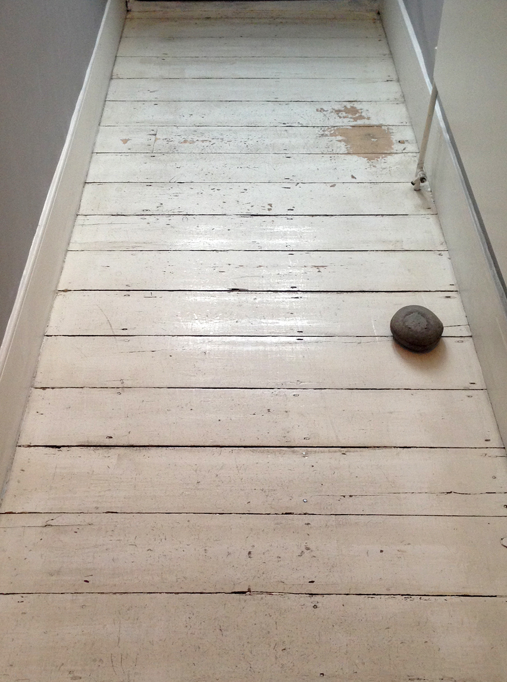 Worn painted floorboards prior to painting