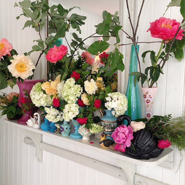 Bright floral display against white backdrop in colourful eclectic home
