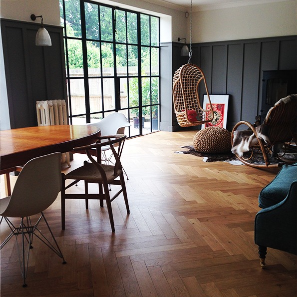 Dining area with herringbone parquet and hanging wicker chair