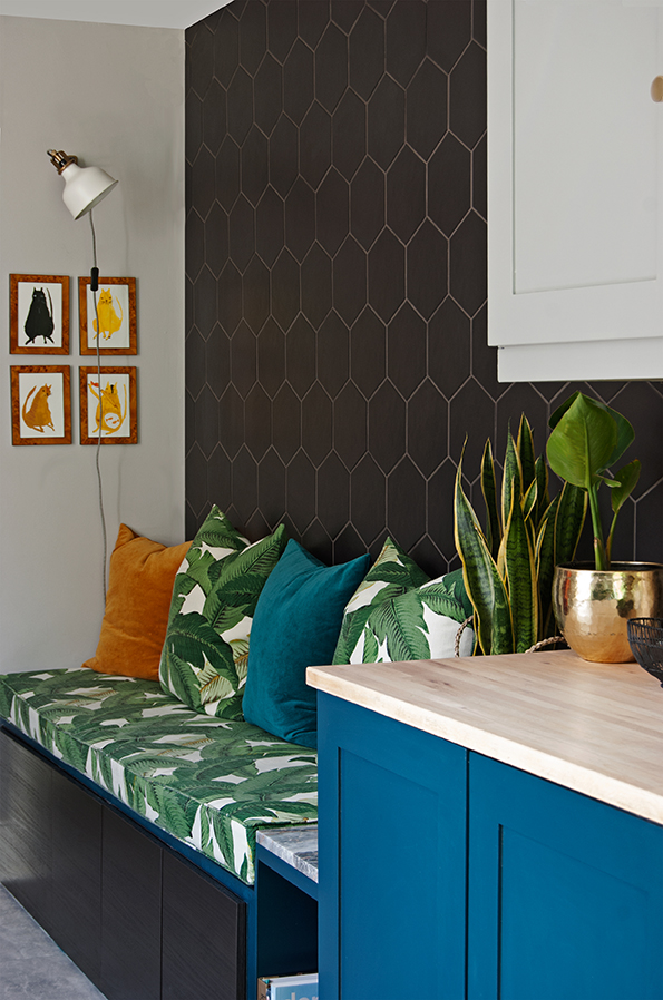 Kitchen bench seat with matt black hex tiled wall and plants