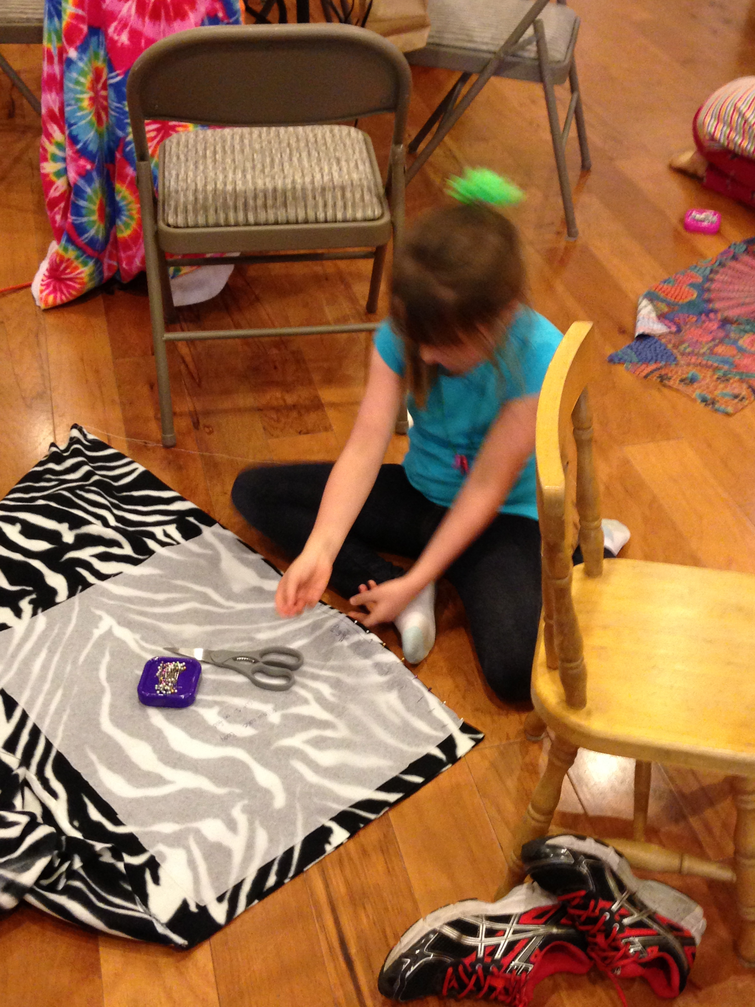 """2nd grader learning how to place a pattern piece that says, """"Place on Fold""""."""