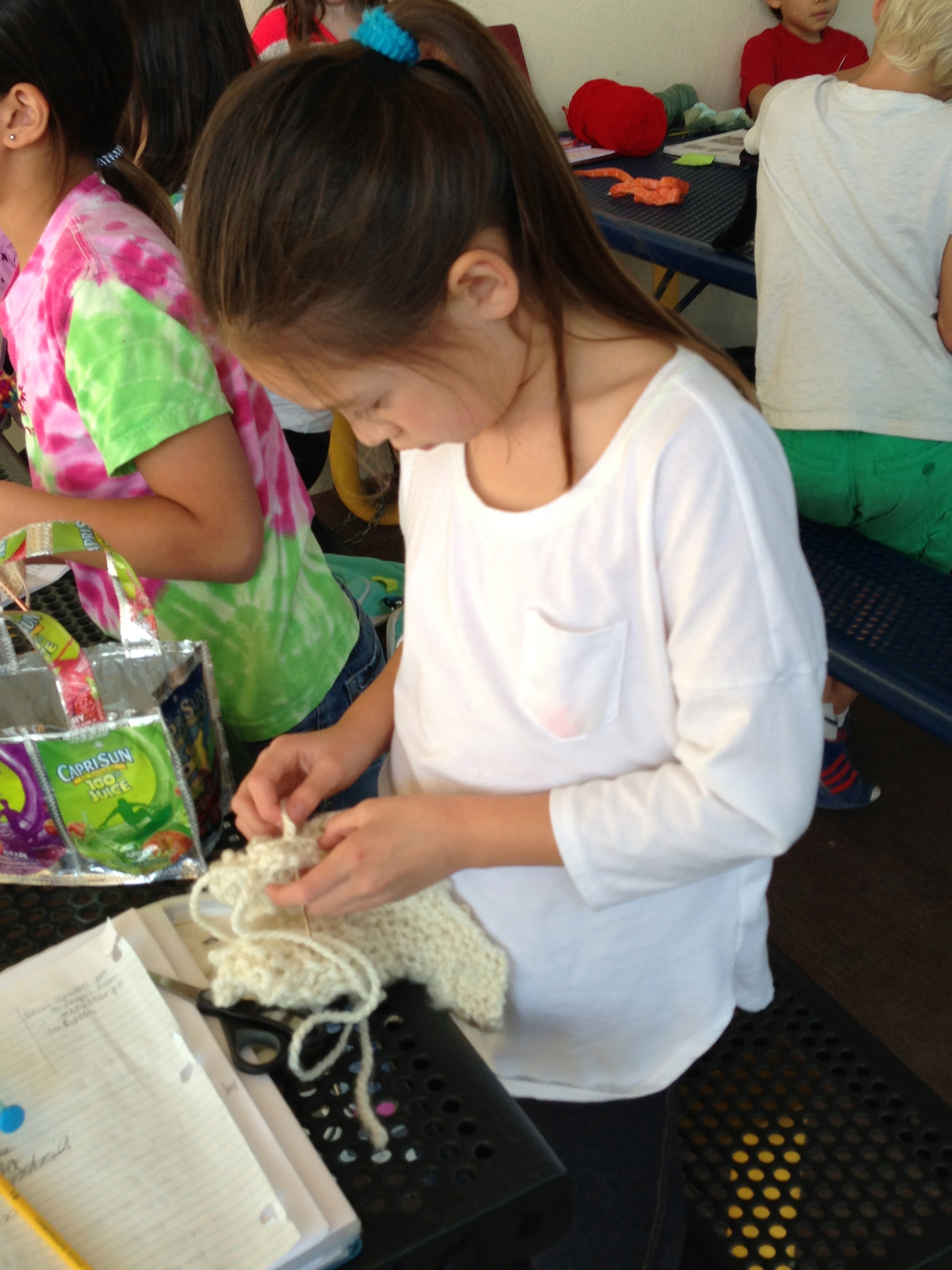 2nd grader sewing her project together.