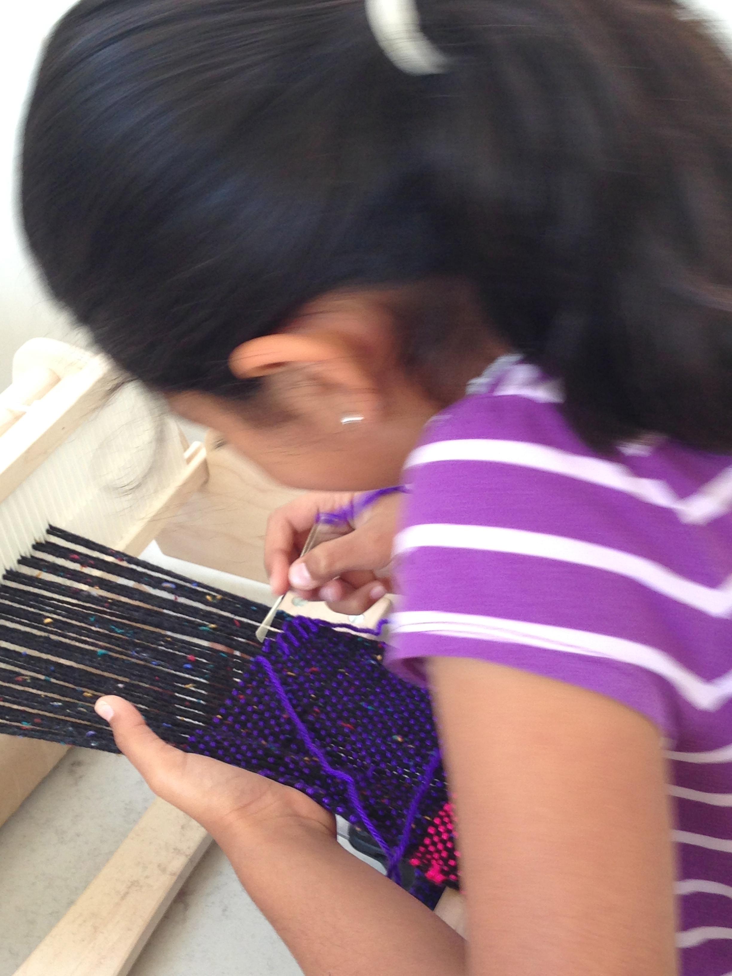 3rd grader hem stitching her scarf.