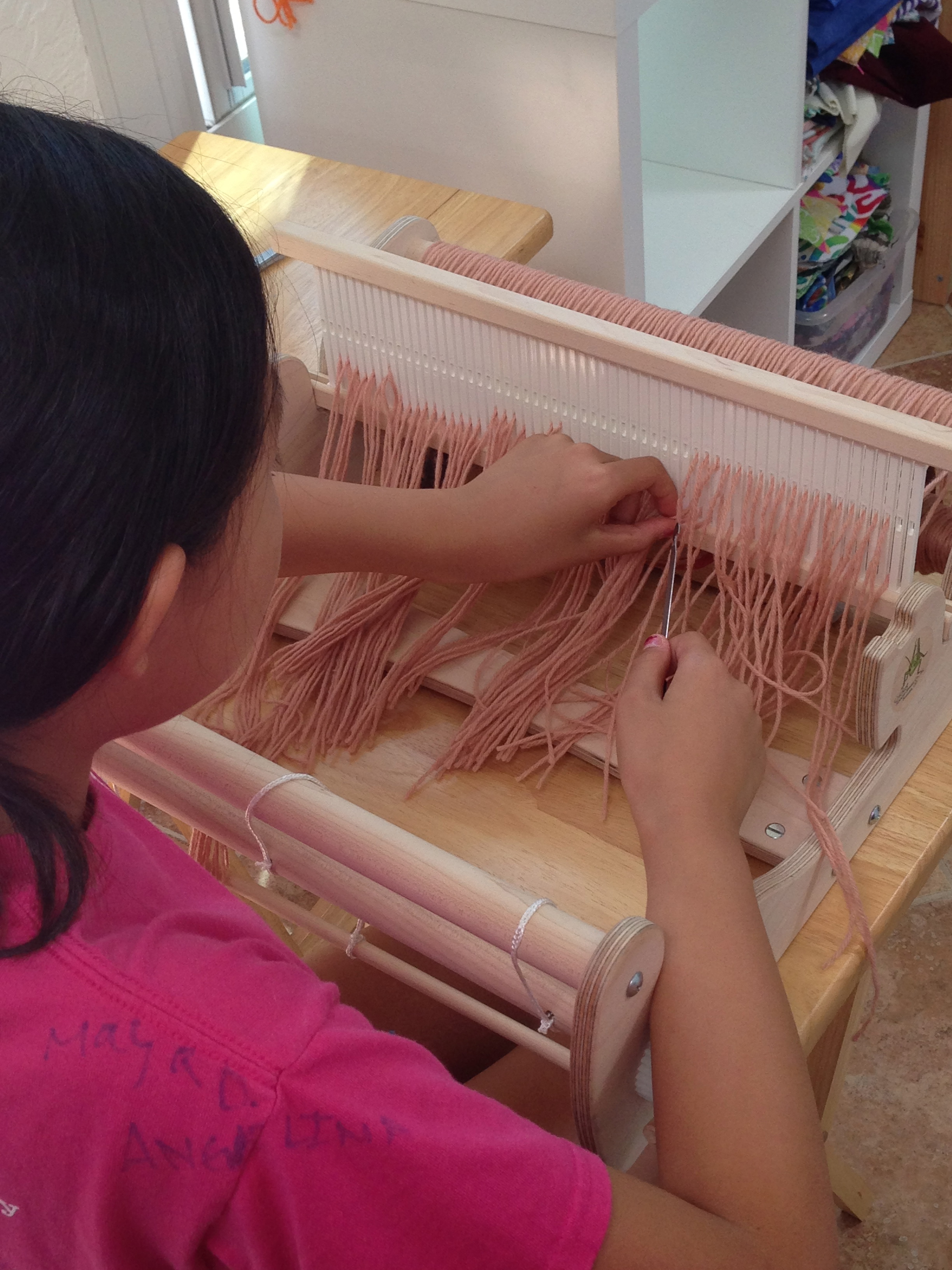 6th grader threading her heddles.