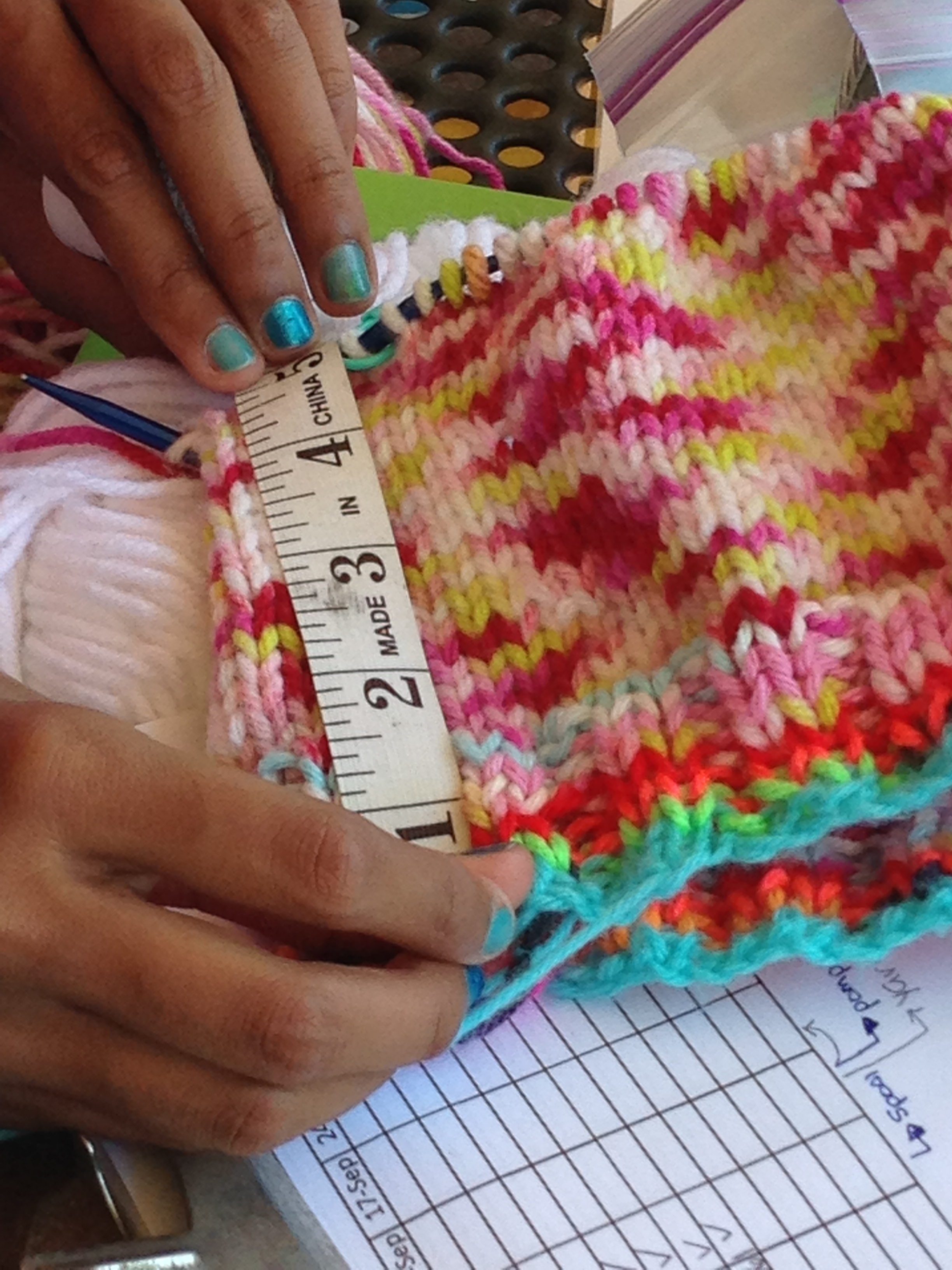 A 4th grader measuring her hat that is being knit in the round on circular needles.