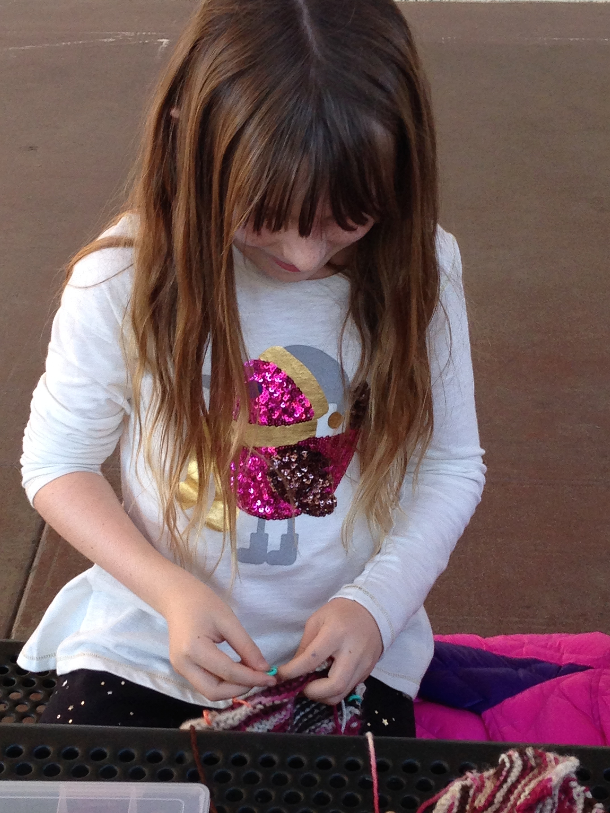 3rd grader sewing up her slippers.