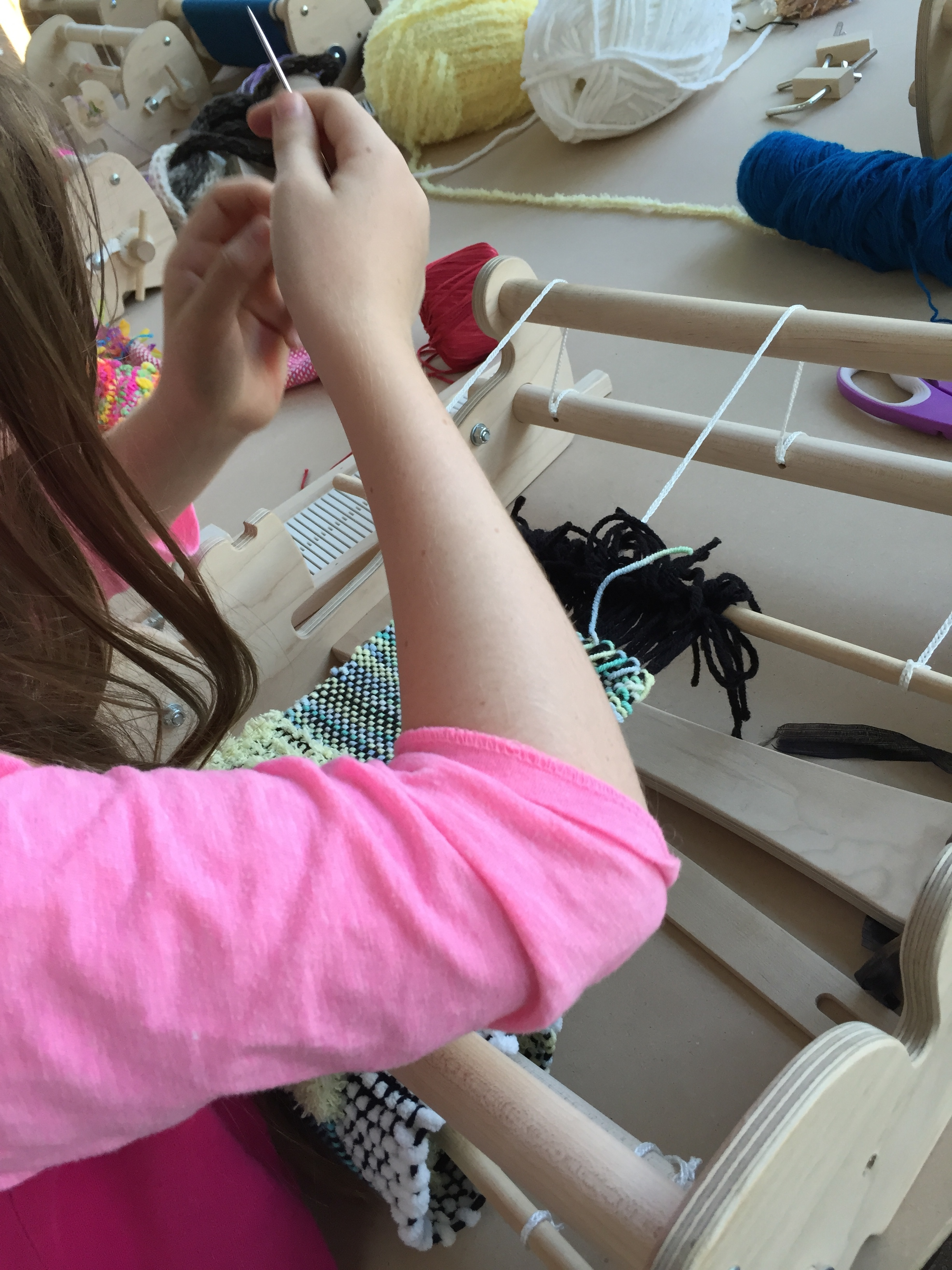 Taking out the waste yarn on her weaving.