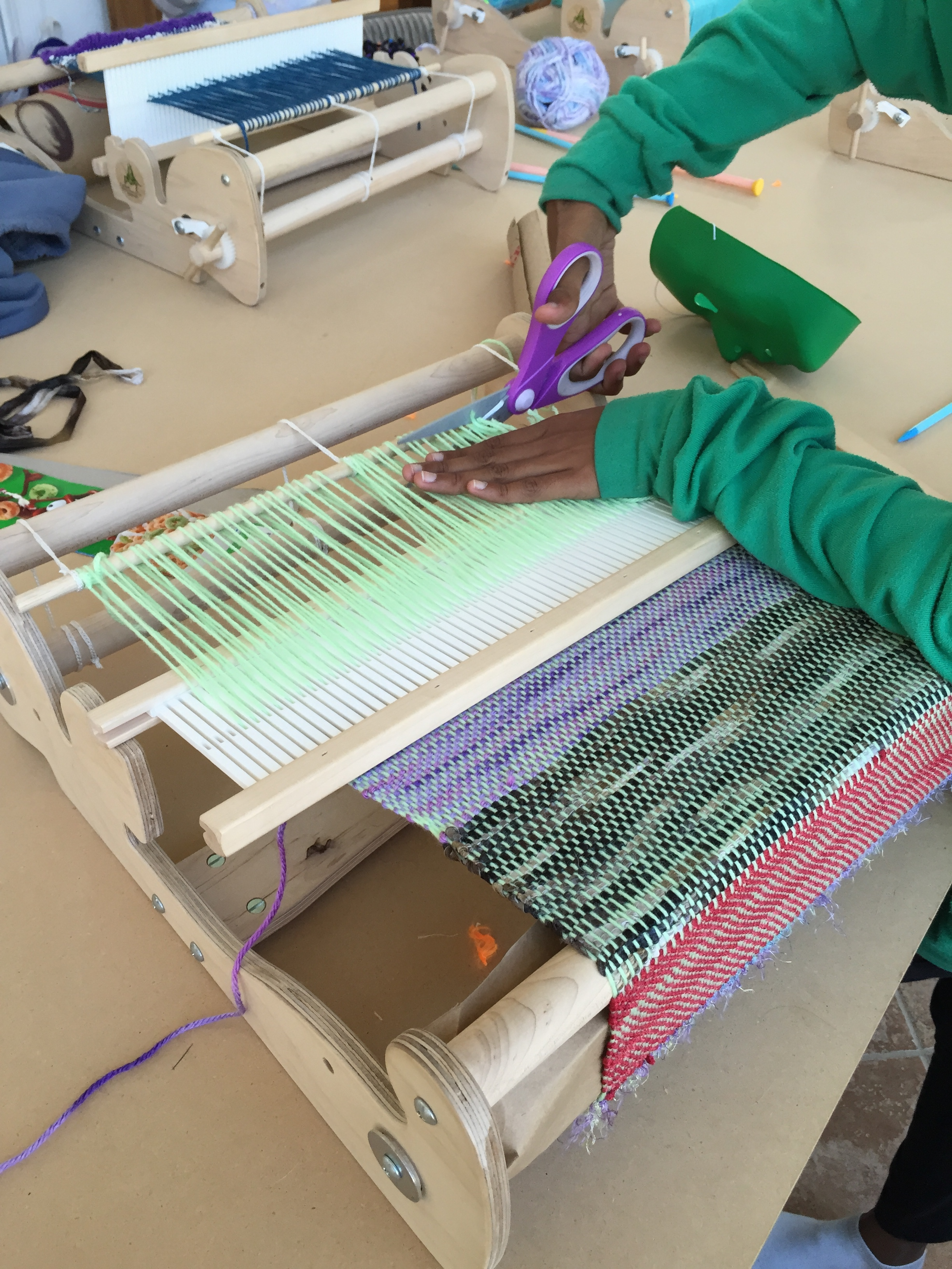 Cutting her weaving off the loom.