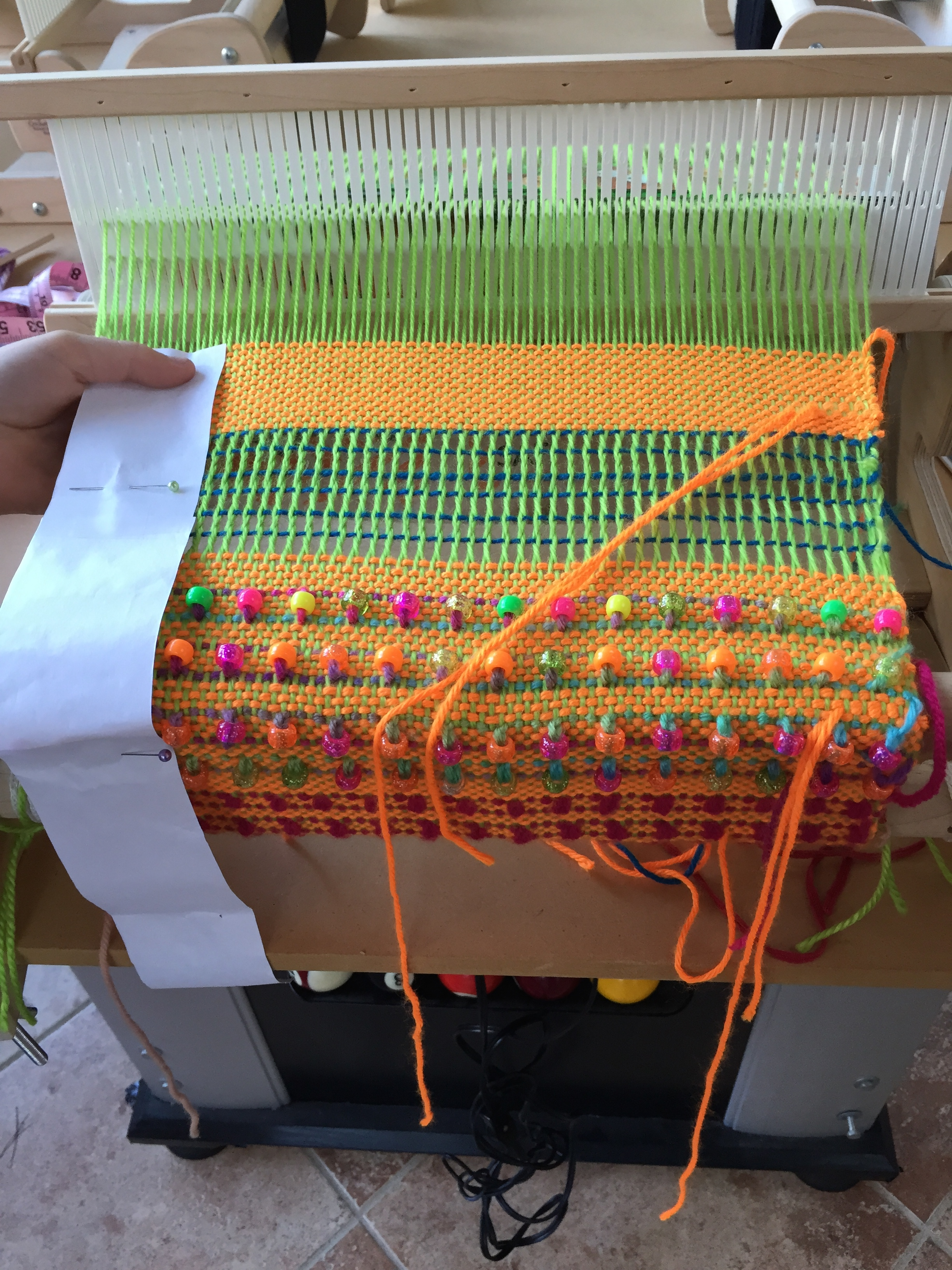 Finishing the weaving on part of a tote bag.