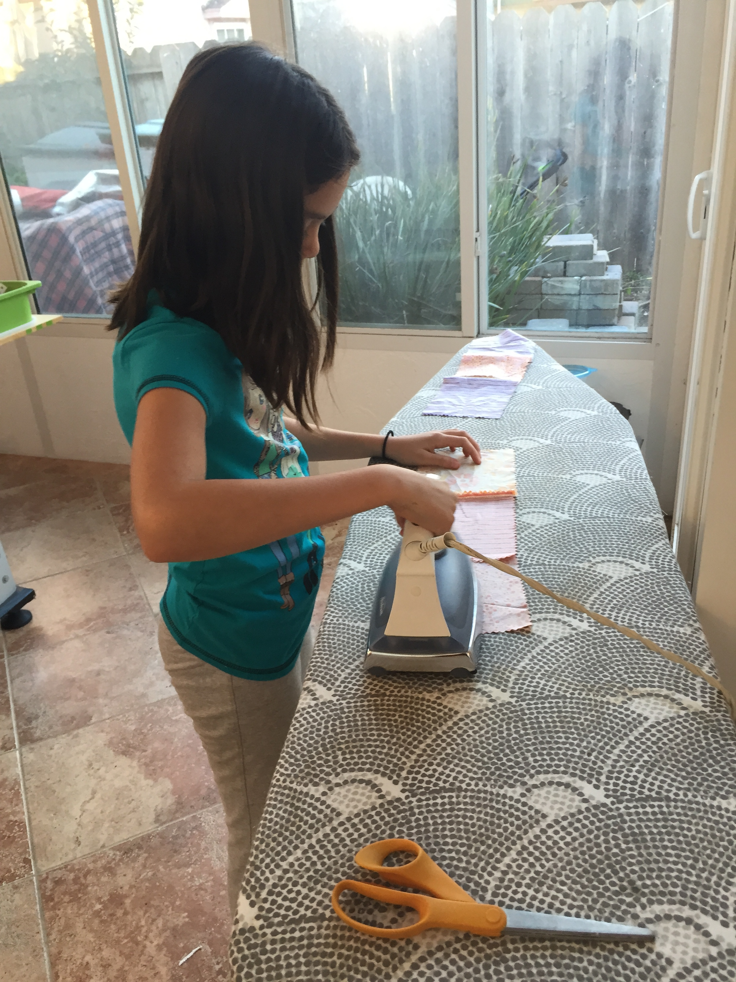 Ironing her quilt pieces.