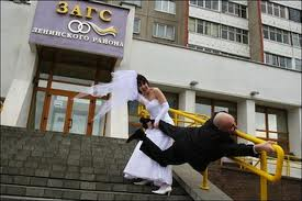 Woman in bridal dress dragging groom who is hanging onto railing up stairs