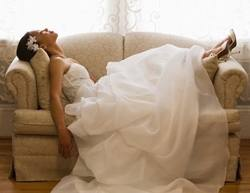 Bride in dress exhasted on couch with feet up