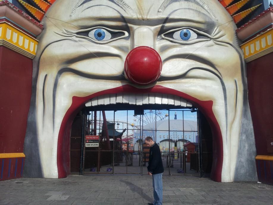 Sad man standing outside Luna park clown face on Melbourne Trip